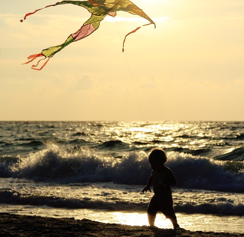 Flying kites as the waves crash.